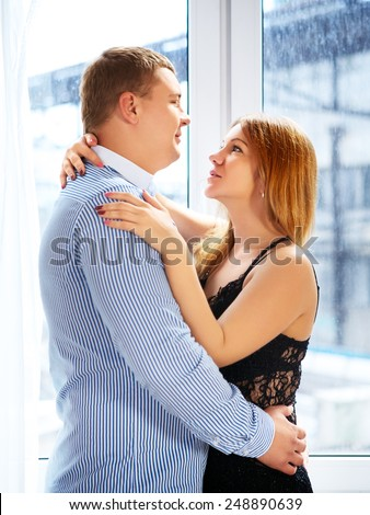 loving mature couple in front of window embrace