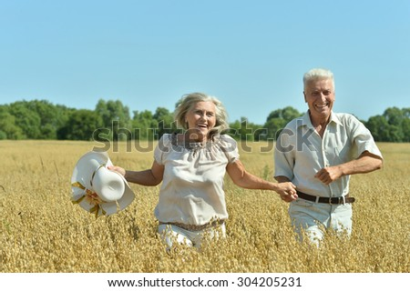 Loving mature couple running  in field  at summer - stock photo