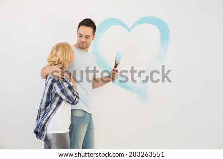 Loving mid-adult couple with painted heart on wall - stock photo