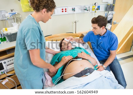 Loving mid adult man wiping forhead of pregnant woman's forehead in hospital - stock photo