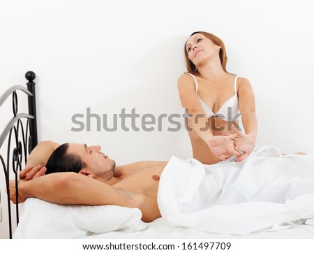 Loving middle-aged couple awaking together on bed in home interior - stock photo