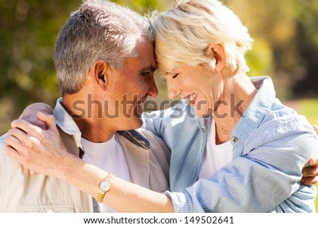 loving middle aged couple hugging with eyes closed closeup portrait - stock photo