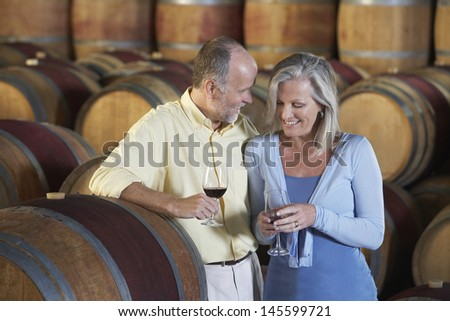 Loving middle aged couple tasting red wine in cellar - stock photo