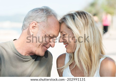 Loving middle-aged couple touching foreheads and smiling happily as they spend a relaxing day at the beach - stock photo
