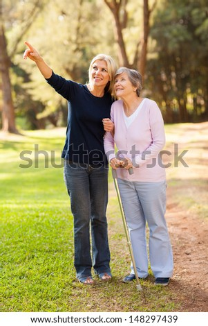 loving middle aged daughter taking senior mother for a walk outdoors in forest - stock photo