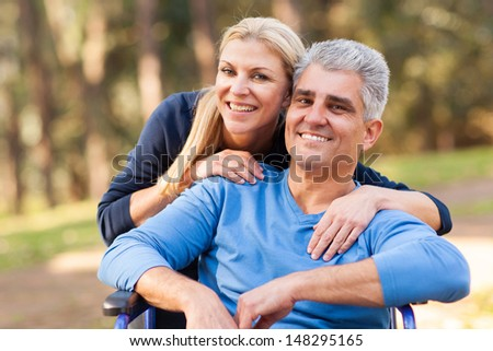 loving middle aged wife and disabled husband outdoors - stock photo