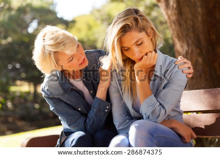 loving middle aged woman comforting her sad daughter at the park - stock photo