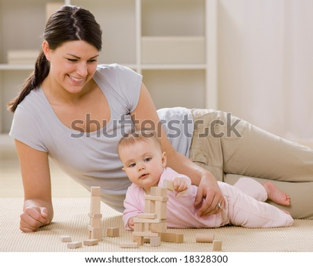 Loving mother and baby playing with wooden blocks on livingroom floor - stock photo