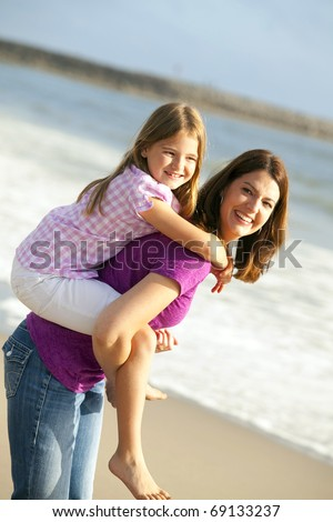 Loving mother and daughter playing on the beach - stock photo