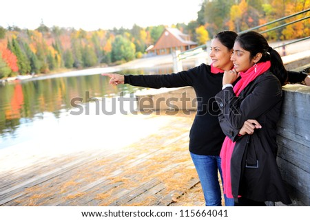 Loving mother and daughter watching something in outdoors - stock photo