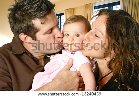 Loving mother and father kissing their baby girl in indoor home setting.