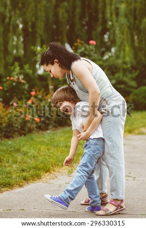 Loving Mother and laughing son playing in summer park - stock photo