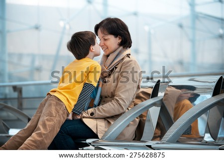 Loving mother and son hugging at airport, going on holiday - stock photo