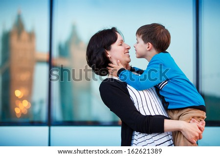 Loving mother and son hugging outdoors in city - stock photo