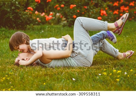Loving Mother and son playing in summer park. Warm toned image - stock photo