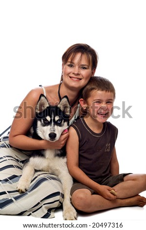 Loving mother and son sitting with their siberian husky pup - stock photo