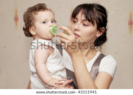 Loving mother feeds baby daughter. - stock photo