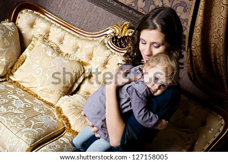 Loving mother holding her infant baby in classic room