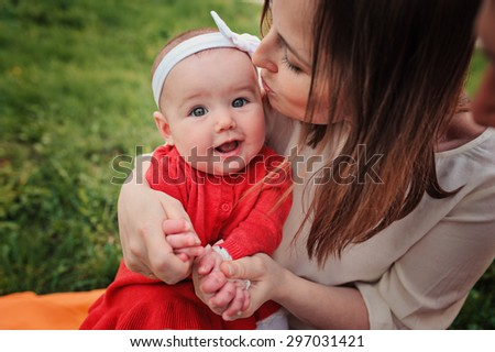 loving mother kisses her happy baby daughter on the walk in summer park