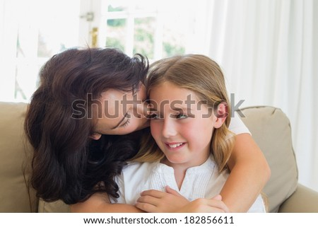 Loving mother kissing cute daughter on sofa at home
