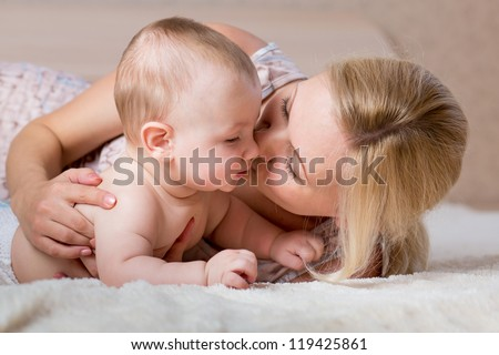 loving mother kissing her baby - stock photo