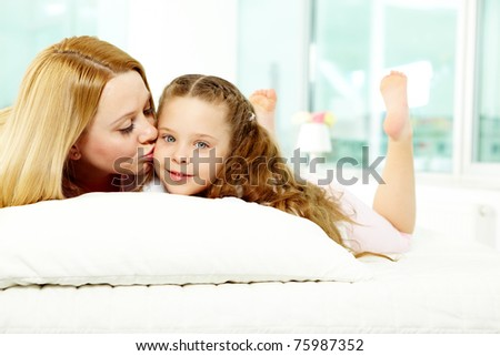 Loving mother kissing her pretty daughter while relaxing on sofa