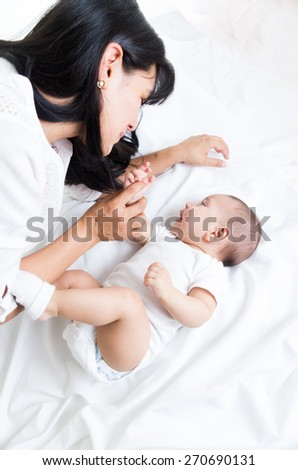 loving mother looking at her adorable baby boy, over the shoulder shot - stock photo