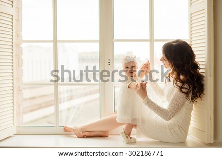 Loving mother playing with her baby sitting on a window - stock photo