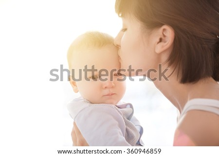 Loving mother playing with her baby sitting on a window with sunrise background - stock photo