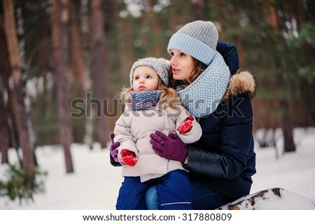 loving mother telling her cute toddler daughter about winter on the walk in snowy forest