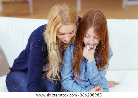 Loving mother with her pretty young daughter sitting close together on a sofa with serious expression looking down as they read something together - stock photo