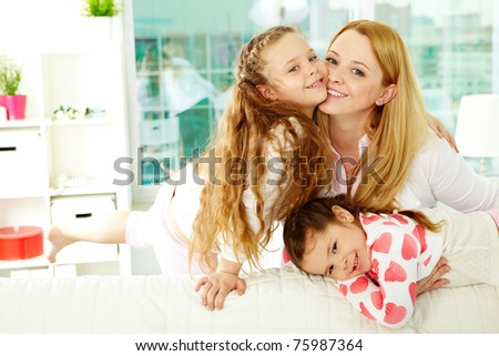 Loving mother with her two pretty daughters having rest at home - stock photo