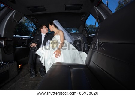 Loving newlywed bride and bridegroom in car - stock photo