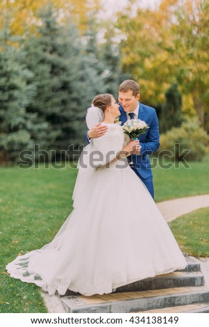 Loving newlywed couple walking in sunny park at alley. Charming bride holding her bridal bouquet - stock photo