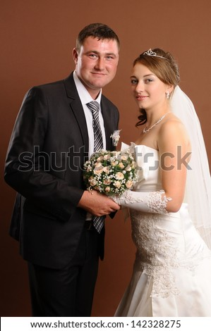 Loving newlyweds standing on a brown background