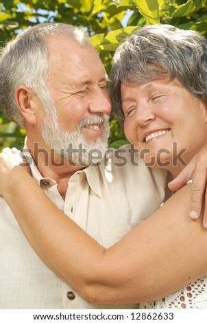 Loving older couple embracing outside and laughing heartily - stock photo