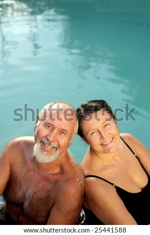 Loving older couple relaxing by the water - stock photo