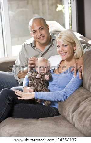 Loving parents with 3 month old baby sitting on lap at home