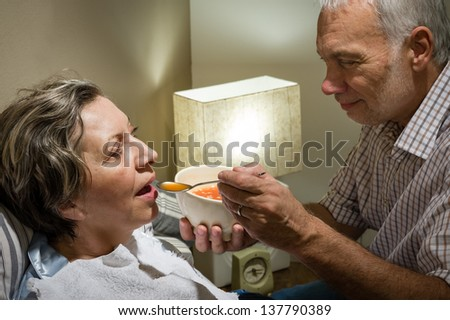 Loving retired husband feeding his ill wife with soup - stock photo