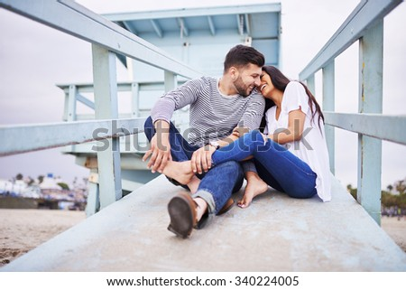 loving romantic Hispanic couple snuggling with each other near santa monica shot with selective focus - stock photo