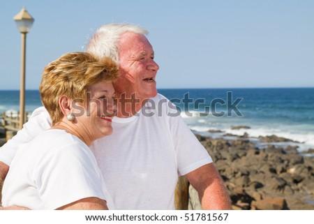 loving senior citizen couple on beach - stock photo