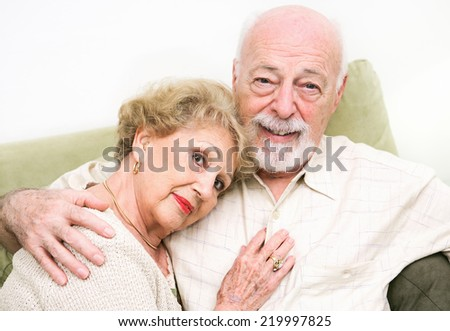Loving senior couple at home relaxing on the couch.