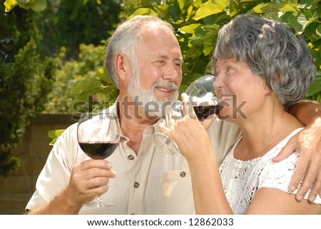 Loving senior couple drinking wine outside