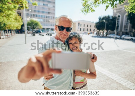 Loving senior couple embracing and taking a selfie on mobile phone outdoors. Tourist taking self portrait during a foreign city vacation. - stock photo