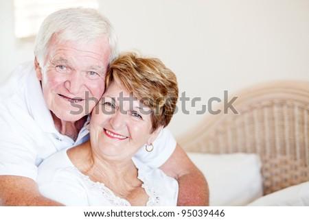 loving senior couple hugging in bedroom - stock photo