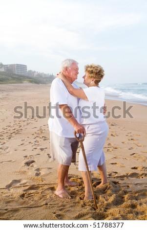 loving senior couple hugging on beach - stock photo