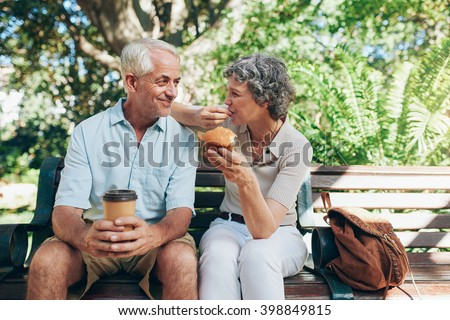 Loving senior couple sitting on a park bench having coffee and muffins. Tourist relaxing outdoors on a park bench. - stock photo