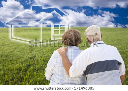 Loving Senior Couple Standing in Grass Field Looking Over at Ghosted House on the Horizon.