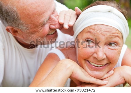 loving senior couple telling secret - stock photo