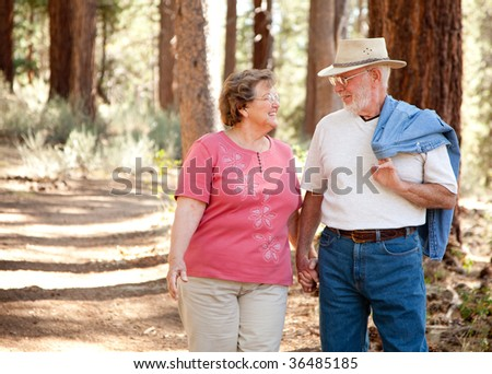 Loving Senior Couple Walking and Enjoying the Outdoors Together. - stock photo